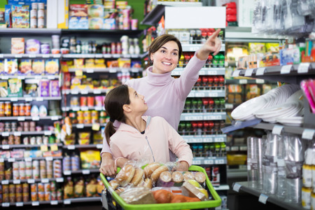Smiling female client with teenage daughter restocking for family in supermarket Stock Photo