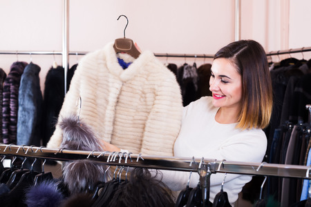 Happy girl deciding on warm mink jacket in women's cloths store