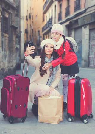 Cheerful woman with daughter making selfie in hats and scarfs with bag