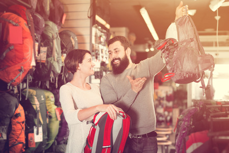 Young couple choosing new rucksack in sports equipment shop. Focus on woman