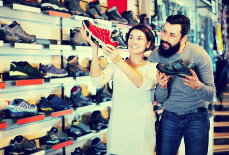 Young couple choosing new sneakers in sports equipment store. Focus on woman