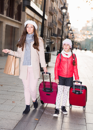 Positive woman with daughter in hats and scarfs walking with bags Stock Photo