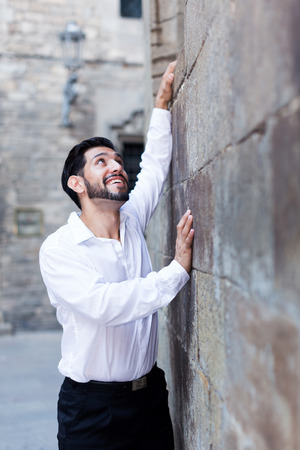 Handsome passionate man standing near old stone wall holding out hands to window