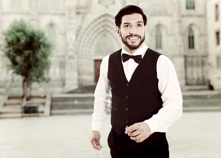 Stylish young man in formal clothes with bow tie posing against old cathedral
