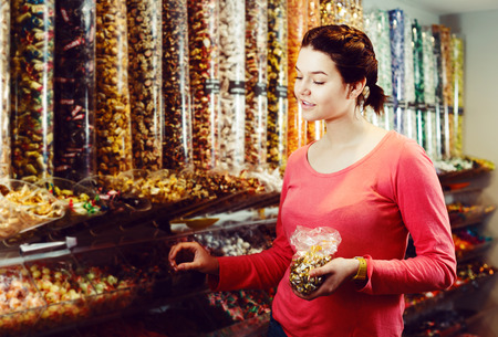 Young positive woman with candies at sweets shop Stock Photo