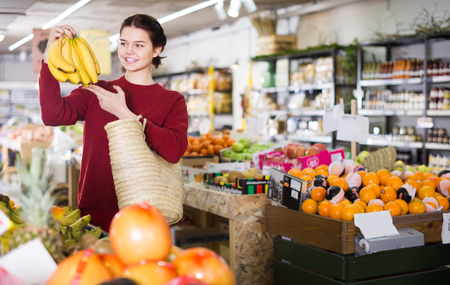 Young customer buys bananas in the fruit department of the store Stock Photo