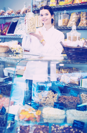 Smiling  girl in uniform  selling candied fruits and nuts