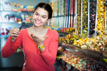 Portrait of young cheerful woman with candies at sweets shop