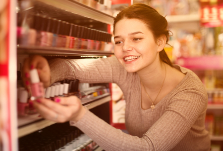 Female customer searching for reliable nail polish in cosmetics shop