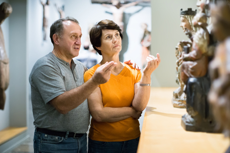 loving senior couple visiting museum of ancient sculpture, inspects the exhibition