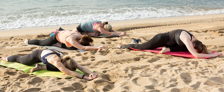 Positive young women practicing yoga positions on beach in sunny day Standard-Bild