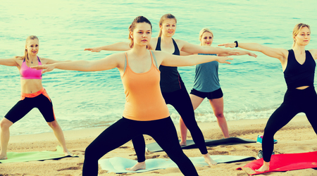 Young slender women exercising yoga poses on sunny beach by ocean Foto de archivo