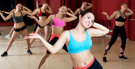 Beautiful young women learn the movements for a new dance in a choreographic studio