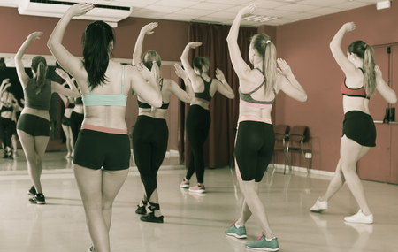 Young slim athletic girls exercising dance training in class