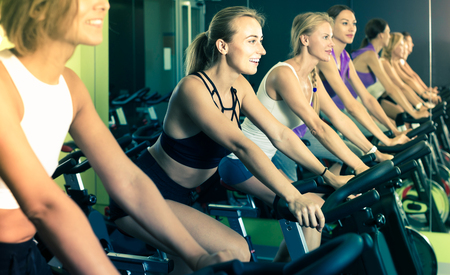 Sporty belorussian  women on cardio training on exercycles in health club