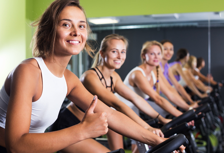 Portrait of satisfied young fit women cycling on stationary bike in gym