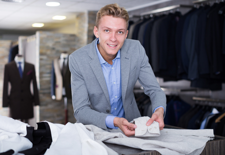 Man buyer in jacket choosing business shirt in the dress shop
