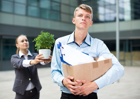 Serious man is standing upset near office because he was dismissaled. Stock Photo