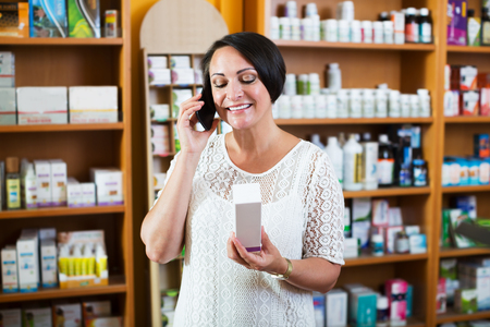 Portrait of smiling mature woman talking using her phone in healthy food store