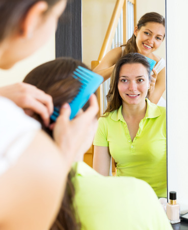 Smiling girls combing the hair in front of mirror