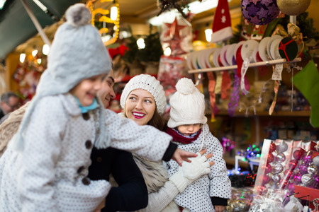 Happy smiling family of four at Christmas market. Selective focus on woman