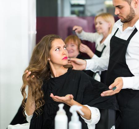Displeased young girl negatively talking with the hairdresser  Reklamní fotografie