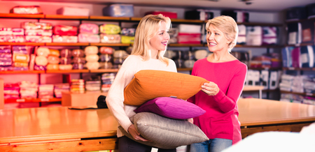 Happy girl and aged mother enjoying purchased pillows in home textile shop Stock Photo