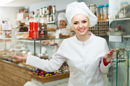 Portrait of friendly smiling woman at the door at confectionery shop   Stock Photo