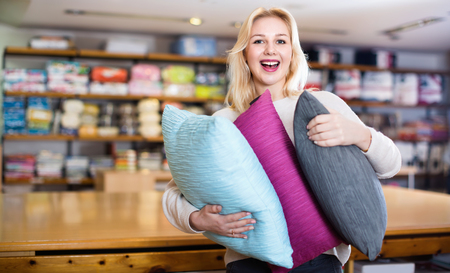 Positive female customer boasting purchased home textiles in textile shop Reklamní fotografie