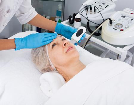 Mujer de edad haciendo procedimientos de belleza para la cara en el salón de spa Foto de archivo