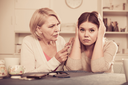 Frustrated middle-aged woman scolds a depressed adult daughter Stock Photo