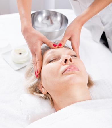 Senior female client enjoying relaxing face massage in beauty salon