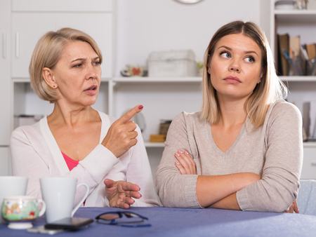 Dissatisfied elderly mother chastises saddened grown-up daughter Stock Photo