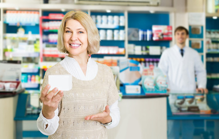 Portrait of smiling mature woman chooses drugs at the pharmacy Stock Photo