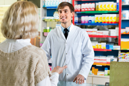 Experienced positive pharmacist counseling female customer in modern farmacy