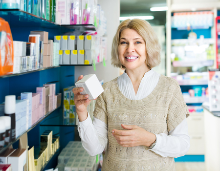 Portrait of american mature woman chooses drugs at the pharmacy