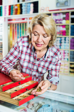 Portrait of mature cheerful female customer standing next to box with metallic fasteners in assortment in a shop  Stock Photo