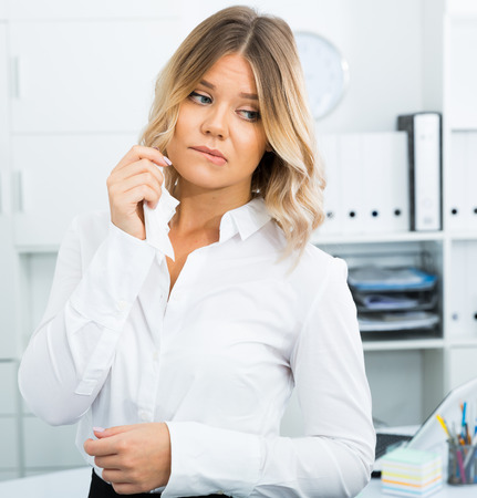 Wistful young woman in white shirt in bright office Stock Photo
