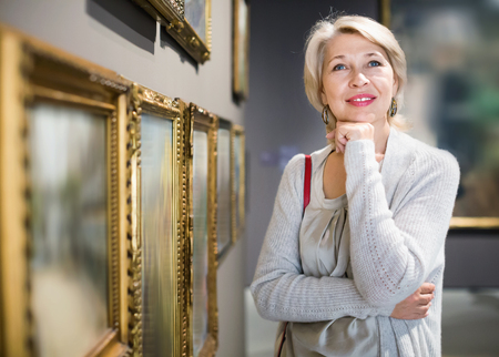Cheerful positive smiling mature woman standing in art museum near the painting in baguette