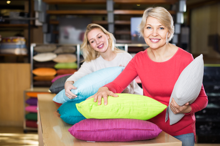 joyous young and senior female customers looking through pillows in home textile shop