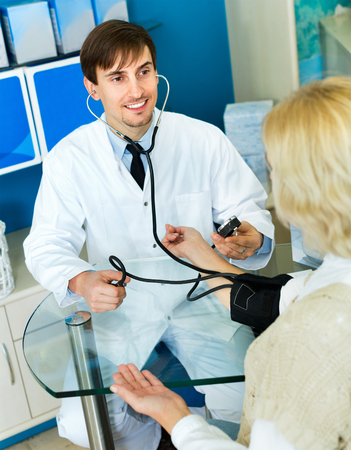 Young friendly male pharmaceutist taking  mature patients blood pressure using  sphygmomanometer in pharmacy drugstore Stock Photo