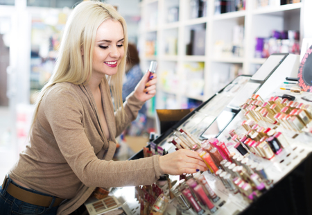 Portrait of young smiling blond woman choosing lip plumper on display