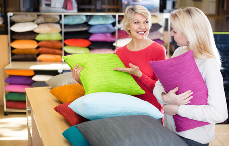 Adult daughter and aged mother choosing pillows in home textile shop