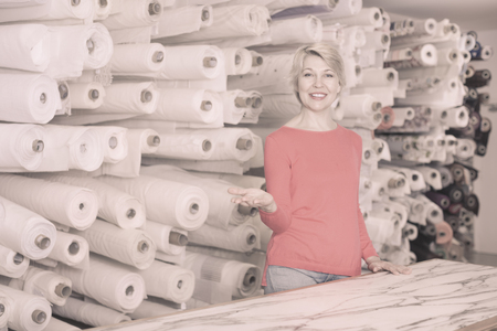 Senior smiling female customer boasting purchased home textiles in textile shop Reklamní fotografie