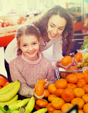 Happy mother and small cheerful daughter buying sweet citrus fruits Stock Photo