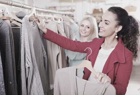 Two cheerful young women choosing basic garments at clothing store