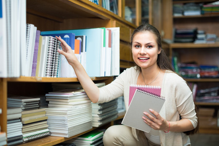 portrait of young cheerful woman choosing copy-books for writing in stationary shop Stock Photo