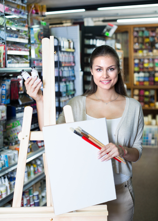 portrait of cheerful woman choosing canvas on easel for drawing in art shop