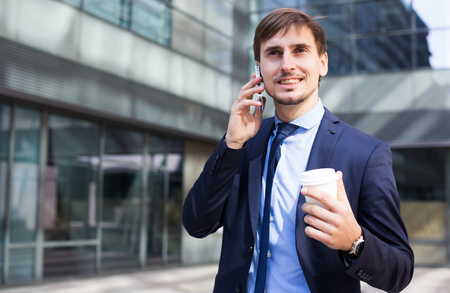 Portrait of cheerful male standing outdoor and talking phone