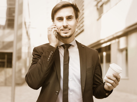 Smiling man worker talking on the phone with coffee on the hand